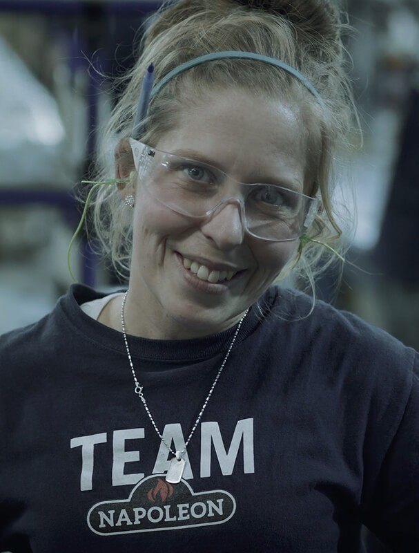 A women smiling at the camera wearing safety glasses and a Napoleon shirt.