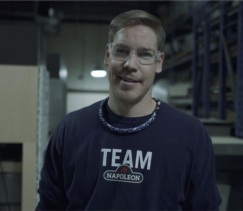 A man smiling at the camera while wearing his safety glasses and Napoleon shirt.
